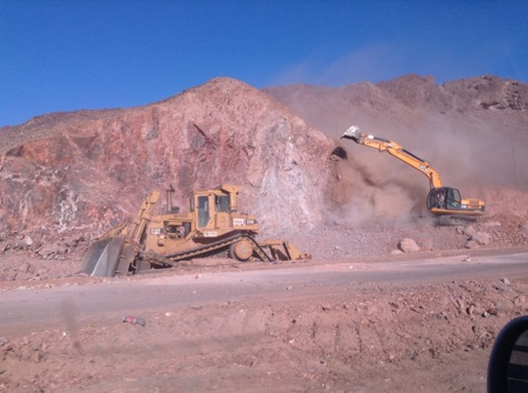 Excavators and bulldozers working to carve out space in the rock.